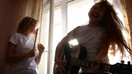 otthonos : Two female teens playing hard rock music with instruments in front the window at home