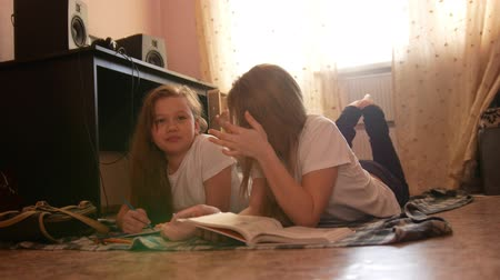 schoolbook : Two girl teens reading a book and drawing while lying on the floor at home