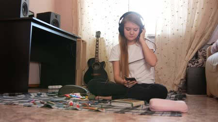 otthonos : Teen girl listening to music in headphones at home Stock mozgókép