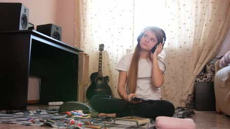 otthonos : Teen girl listening to music in headphones using smartphone sitting on the floor at home