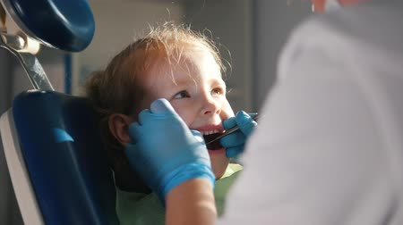 toolbox : Happy little girl sitting in dental chair, stomatologist examining her teeth