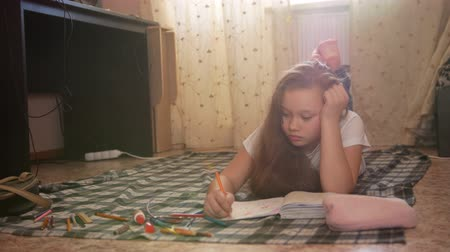 schoolbook : Girl teen who spend time at home drawing while lying on the floor Stock Footage