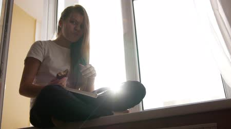 schoolbook : Pretty young blonde girl eats cake and flipping through the book sitting on the windowsill Stock Footage