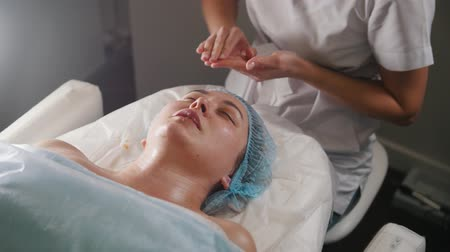 cleaning products : Cosmetologist applying oil on the clients neck and shoulders after cosmetic procedure Stock Footage