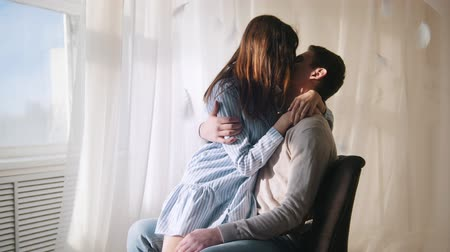 düşünceli : Young guy and girl sitting by the window in a brightly lit room, hugging and kissing Stok Video