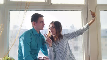 düşünceli : Young and attractive man and woman doing a selfie sitting at the window
