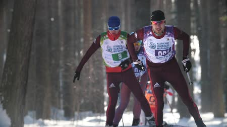 deslizamento : KAZAN, RUSSIA - March, 2018: Athletes skiers running Kazan ski marathon in the winter woods