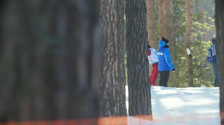 deslizamento : KAZAN, RUSSIA - March, 2018: slow motion of male participant winter ski marathon fast running past the trees, volunteers and spectators and drinking hot drinks Vídeos