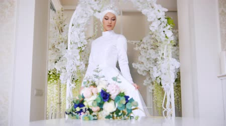 оформление : Beautiful bride in white traditional muslim dress with bunch of flowers