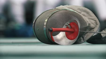 meç : Fencing protective mask and rapier on the floor during fencing competition Stok Video