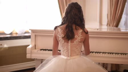 mulher jovem : Young lady in evening dress in ballroom playing the piano - rear view Vídeos