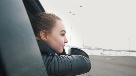 admirado : Happy woman leans in the car window admired at the beautiful sights of the city