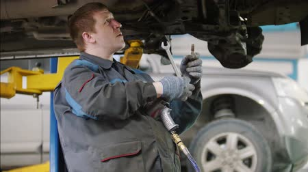 машиностроение : Mechanic unscrews detail of car in hood - automobile service repairing, close up