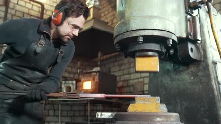 ручная работа : Molten metal is processed under pressure in the hands of a blacksmith, wide angle
