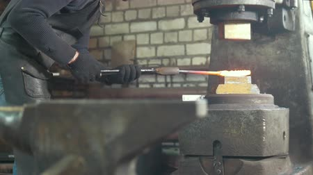 roztavený : Man blacksmith forges the metal at the mechanical hammer