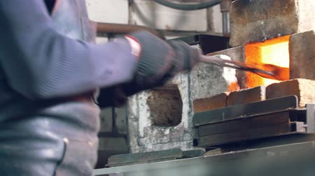 labour : Blacksmith with gloves in forge makes steel knife