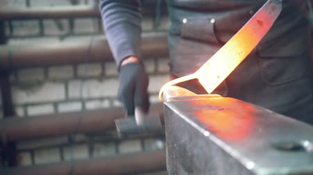 ferramenta : The blacksmith shaping hot steel with a hammer in the workshop Vídeos