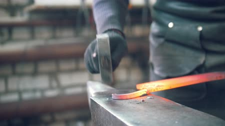 ручная работа : The blacksmith shaping the molten hot steel with a hammer on the anvil