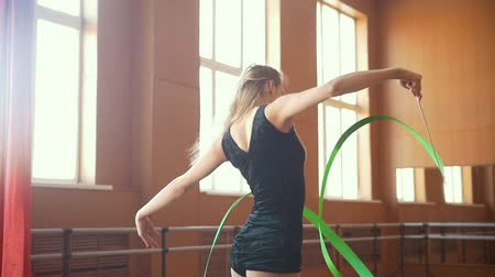 ритмичный : Young blond hair woman trains with a green ribbon - gymnastics exercise in studio with mirror Стоковые видеозаписи