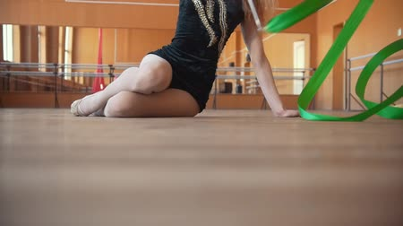 çevik : Woman sitting on the floor performing exercise with a ribbon