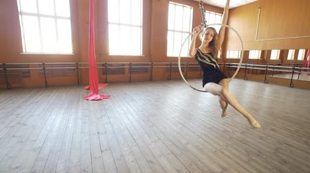 çevik : Beautiful ballerina swinging on aerial hoop in a classroom