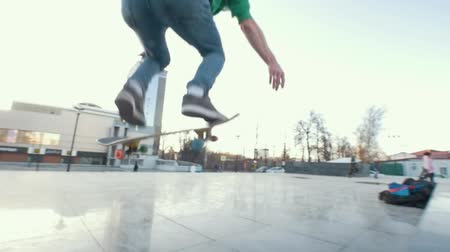 kickflip : Skateboarder does kickflip on his board in city street at sunset Stock Footage