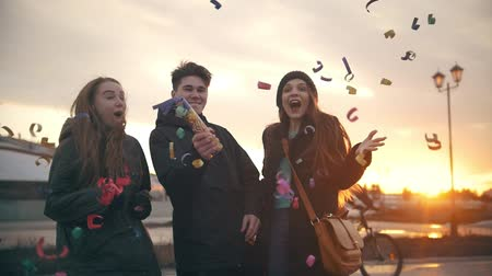 hipster : Young friends laughing and having fun with confetti outdoors