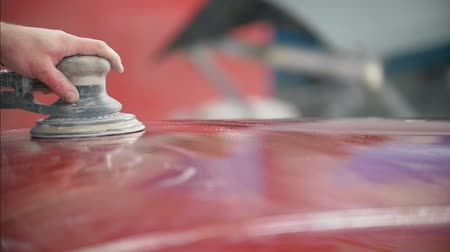 repair : Professional car service - a worker polishes red automobile Stock Footage