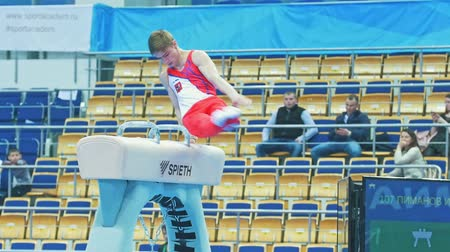 participante : KAZAN, RUSSIA - APRIL 18, 2018: All-Russian gymnastics championship - Young male athlete performing on pommel horse