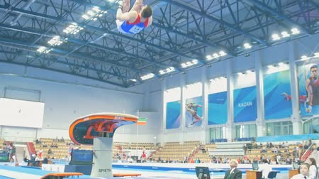 participante : KAZAN, RUSSIA - APRIL 18, 2018: All-Russian gymnastics championship - Young male athlete performing a leap at the stadium