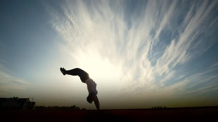 backflip : Young man performing somersault in front of the sun, slow-motion