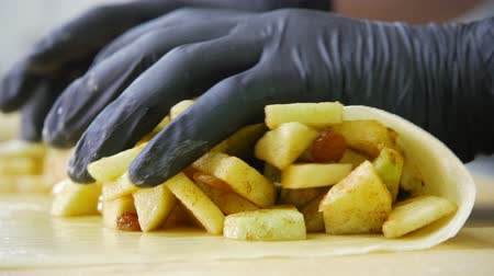 испечь : Cook prepares fresh apple in dough for pie strudel