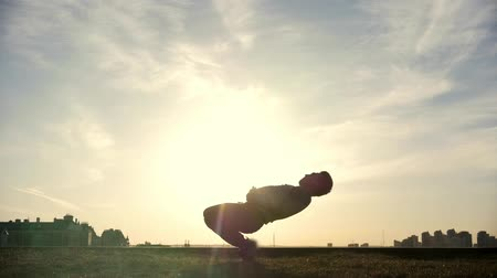 urbex : Slow-motion - young male Parkour tricker jumper performs amazing flips in front of the sun Stock Footage