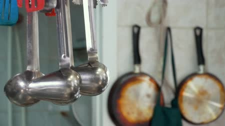 suporte : Griddles and skimmers hanging on holder in restaurant kitchen