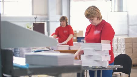 časopis : Female workers sorting a paper stacks in the typography
