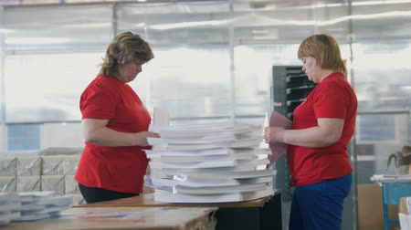 nakladatelství : Female workers sorting a paper stacks in the typography