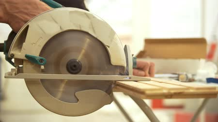 parafusos : Carpenter working with circular blade sawing the wooden piece