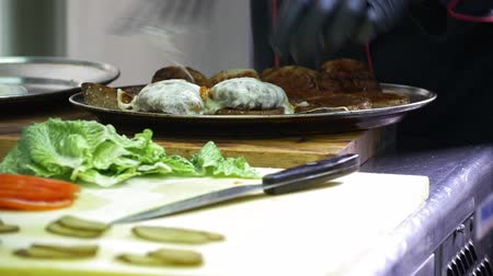 civakodás : Hands of chief on commercial kitchen serves burgers on the plate - inside the restaurant Stock mozgókép
