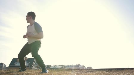 urbex : Young manParkour tricker jumper doing warm-up before training in front of the sun