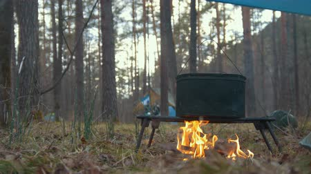 panelas : Cooking food in black iron cauldron on the campfire in forest