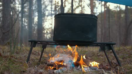 panelas : Cooking food in black boiler on the bonfire in the forest - man put in plastic trash into campfire Stock Footage