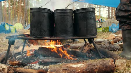 panelas : Three black iron cauldrons on the bonfire for cooking food Stock Footage