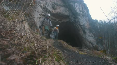 kijárat : Young hikers in helmets coming out from the dark cave with flashlights