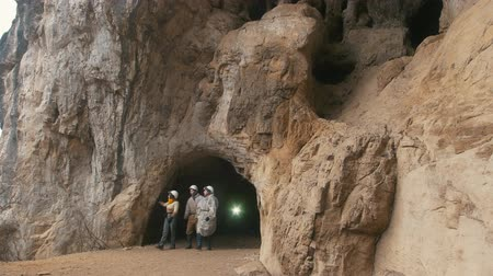 çıkmak : Young explorers in helmets coming out from the large dark cave