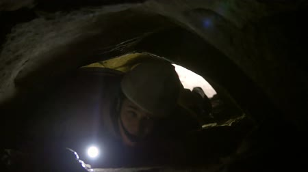 fearless : Young man crawls through narrow hole in cave with flashlight in his hand