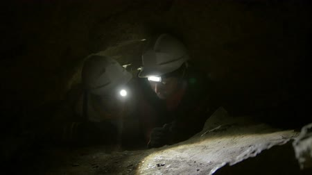 fearless : Two young hikers explorers stuck in the narrow hole in dark cave