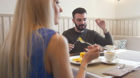 tentar : Young caucasian man in front of woman tries desserts in the cafe Stock Footage