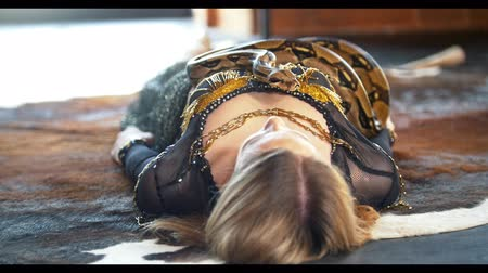 színésznő : Beautiful circus actress lying on the floor with python in a studio