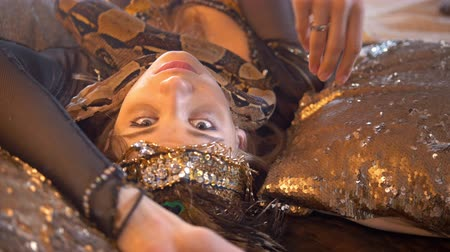 scena : Python crawling on the face of young female dancer in bright costume