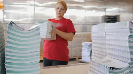 nakladatelství : Female worker looking through printed magazines and puts on in stacks in the typography